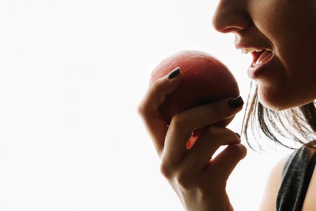Frau isst roten apfel