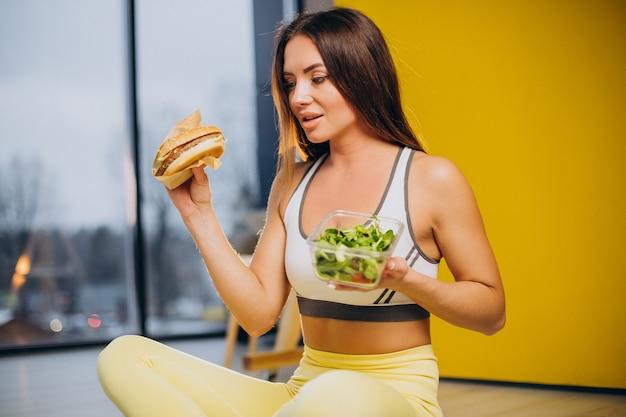 Frau isst salat isoliert auf gelbem hintergrund