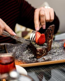 Frau isst schokoladenkuchen mit erdbeerscheiben auf der oberseite