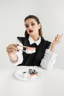 Frau isst sushi aus kunststoff, öko-konzept. organische welt verlieren.