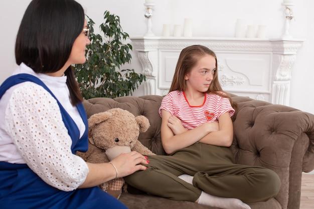 Frau ist eine professionelle kinderpsychologin, die mit einem teenager-mädchen in ihrem gemütlichen büro spricht