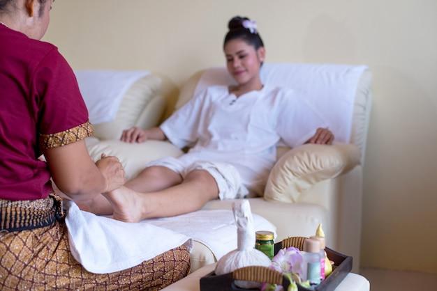 Frau ist glücklich, in der greflexology fußmassage im wellnessbadekurort zu genießen