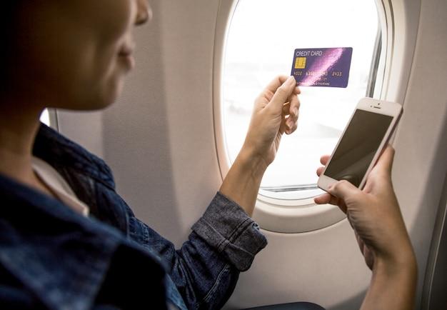 Frau ist hand hält eine kreditkarte und ein smartphone im flugzeug.