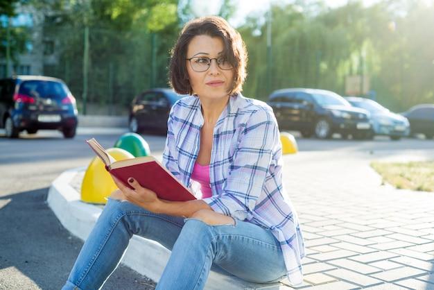 Frau ist in der stadt entspannend, die ein buch liest