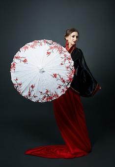 Frau ist in rote chinesische japanische volkskleidung gekleidet. fliegender stoff, schöner regenschirm und fächer im japanisch-chinesischen stil, lange ohrringe in den ohren.