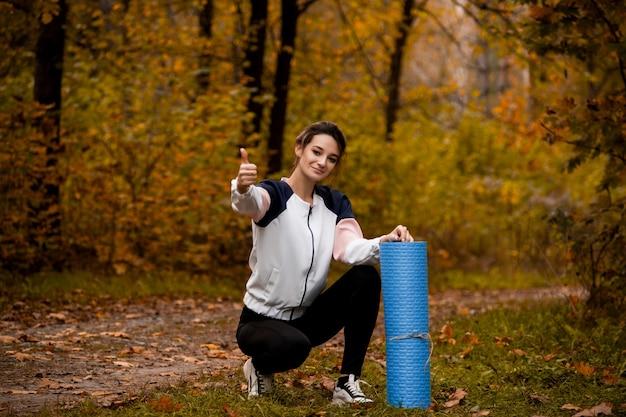 Frau ist mit ihrem training zufrieden. wald oder park in der rückenform. junge passende frau, die oben thrombt und in der nähe ihrer yogamatte sitzt. herbstwald. yoga praktizieren. dehnen vor dem joggen.