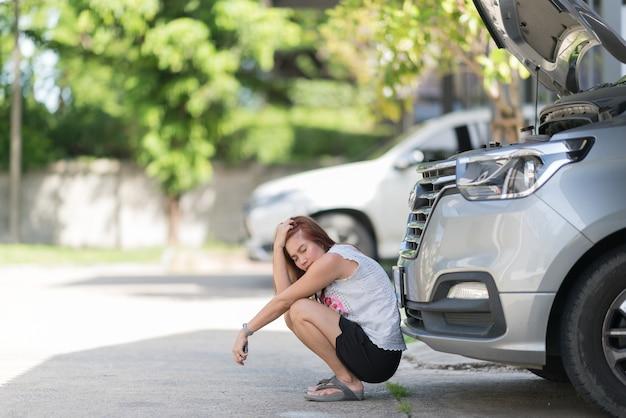 Frau ist traurig wegen eines kaputten autos
