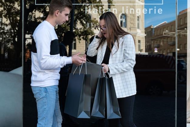 Frau ist überrascht und erfreut über die einkäufe ihres mannes. glücklicher blick der jungen frau in eine einkaufstasche.