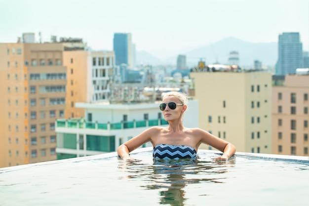 Frau jung schön auf dem dach des hotels im pool mit blick auf die stadt