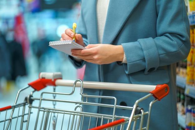 Frau käufer mit wagen im ladengang mit einkaufsliste während des einkaufens von lebensmitteln