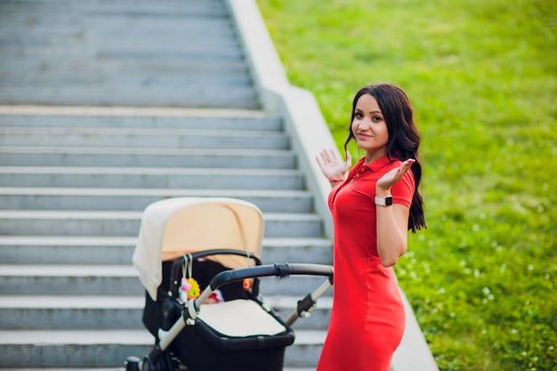 Frau kann einen kinderwagen nicht anheben. moderner kinderwagen. treppen ohne hubrahmen für rollstühle für kinder und behinderte. eine schwierige situation. keine komfortable stadt