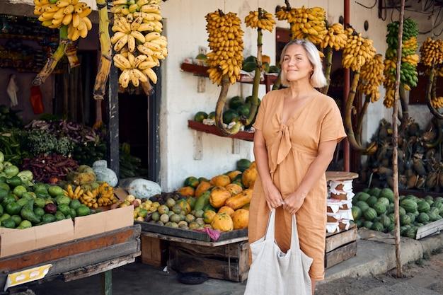 Frau kaufen frisches obst am exotischen lokalen markt
