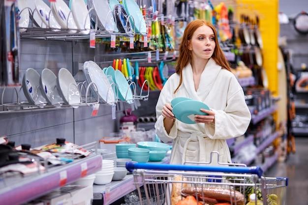 Frau kauft auswahlplatten im supermarkt und vergleicht die schönsten. frau im bademantel beim einkaufen