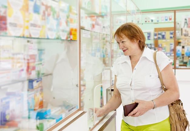Frau kauft drogen in der apotheke