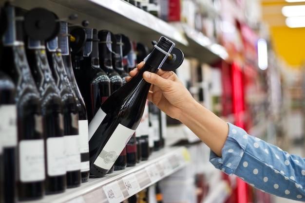 Frau kauft eine flasche wein am supermarkthintergrund