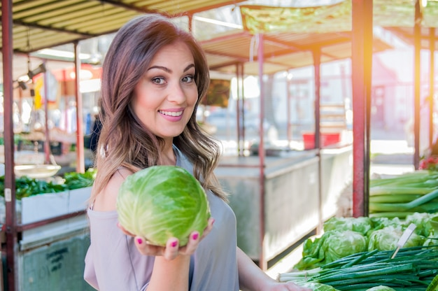 Frau kauft frisches bio-gemüse am straßenmarkt. junge frau kauft gemüse auf dem grünen markt.