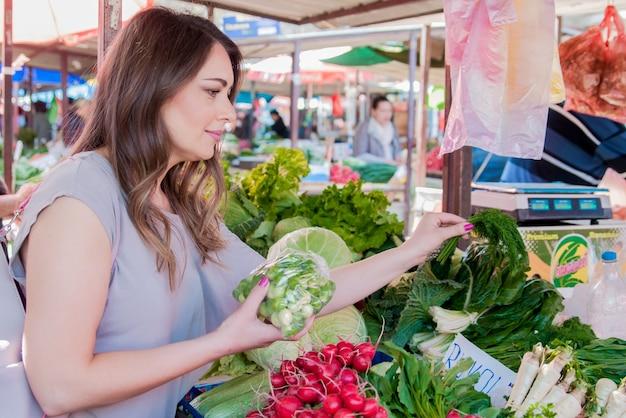 Frau kauft frisches bio-gemüse am straßenmarkt. lächelnde frau mit gemüse auf marktgeschäft. konzept der gesunden lebensmittel einkaufen