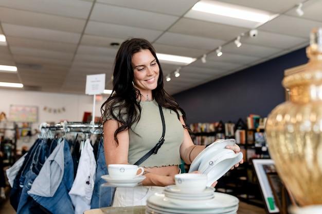 Frau kauft haushaltswaren in einem second-hand-laden