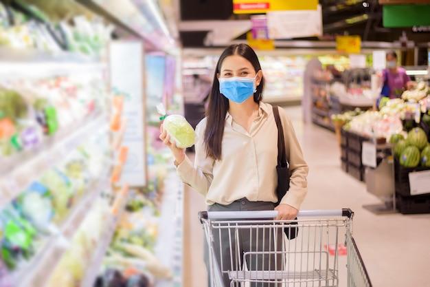 Frau kauft im supermarkt mit gesichtsmaske ein