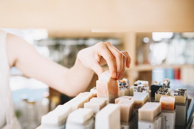 Frau kauft körperpflegeartikel in zero waste shop öko-bio-kosmetik im lokalen geschäft