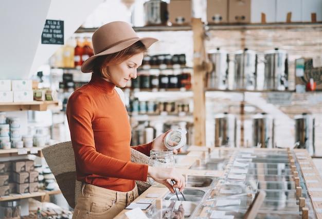 Frau kauft lokale produkte im plastikfreien lebensmittelgeschäft zero waste shop