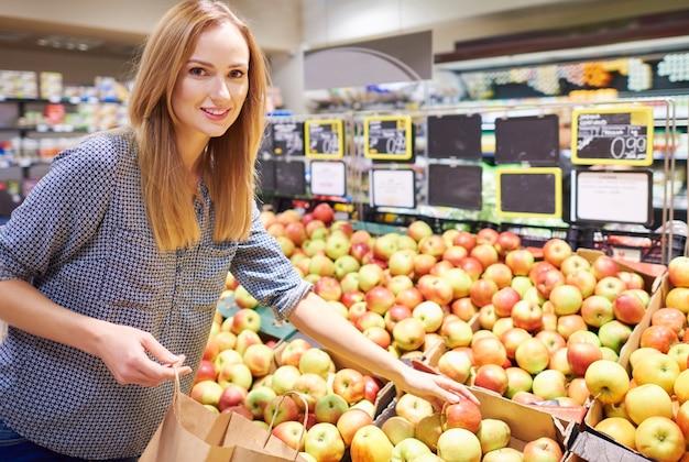 Frau kauft reife und leckere äpfel