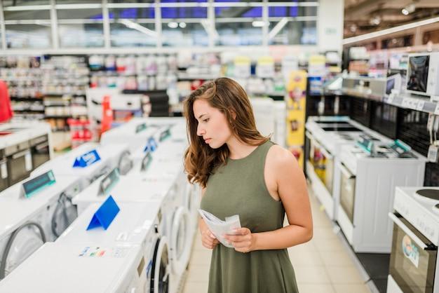 Frau kauft waschmaschine in einem speicher und hält handbuch.