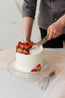 Frau kellner schneidet mit einem messer weiße sahnetorte mit erdbeeren auf dem tisch