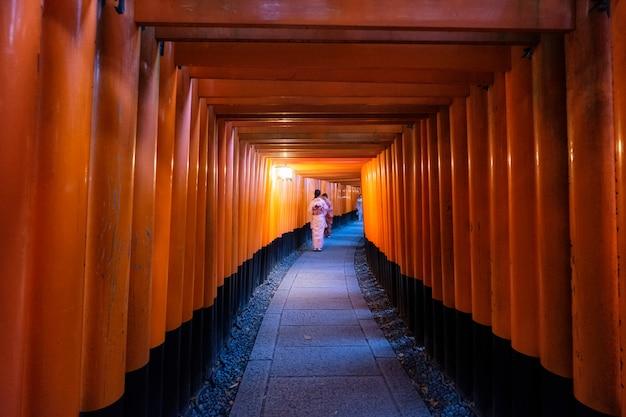 Frau kleidete den kimono, der in rotes altes hölzernes torii tor an schrein fushimi inari geht