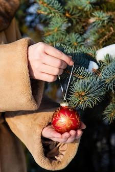 Frau kleidete in einem pelzmantel an, der einen roten weihnachtsball auf tannennahaufnahme hängt