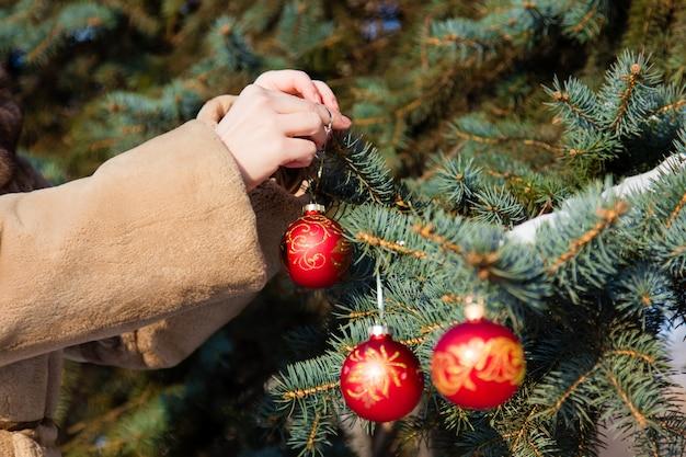 Frau kleidete in einem pelzmantel an, der weihnachtsdekorationen auf tannennahaufnahme hängt. grußkarten-konzept des neuen jahres. geringe schärfentiefe