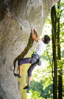 Frau kletterer auf ihrem anspruchsvollen weg, bouldern