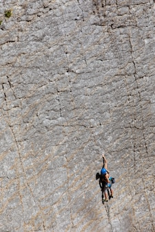 Frau klettert auf einen steilen berg