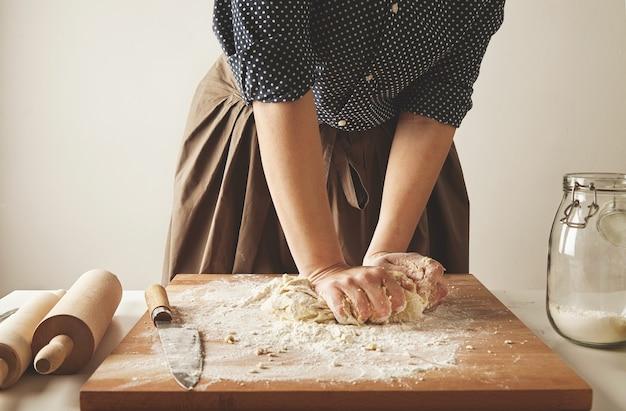 Frau knetet teig für nudeln auf holzbrett nahe zwei nudelhölzern und glas mit mehl