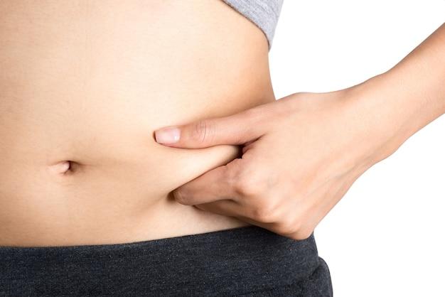 Frau kniff ihre cellulite auf magen - verlieren sie gewicht- überladen sie und gesundes körperkonzept.