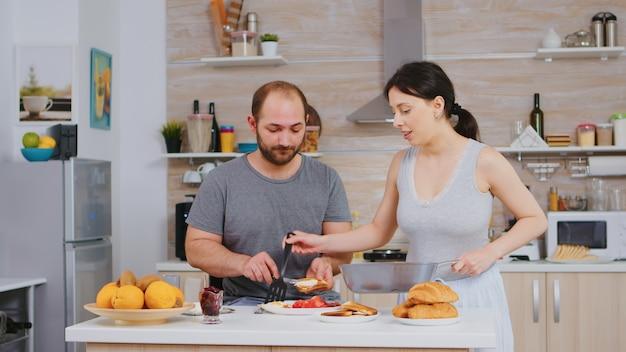 Frau kocht eier für ehemann während des frühstücks, während er butter auf geröstetes brot schmiert. morgens pyjamas tragen, gemeinsames essen zubereiten, junges glückliches paar lieben und heiraten