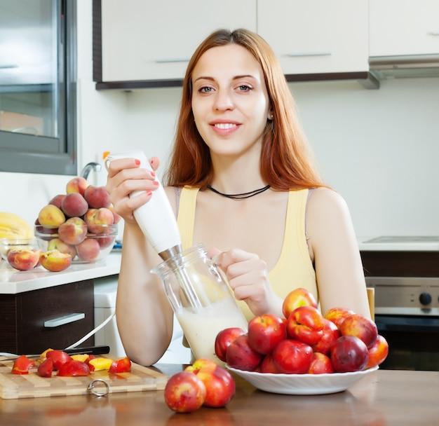 Frau kocht milchgetränke mit nektarinen in der küche