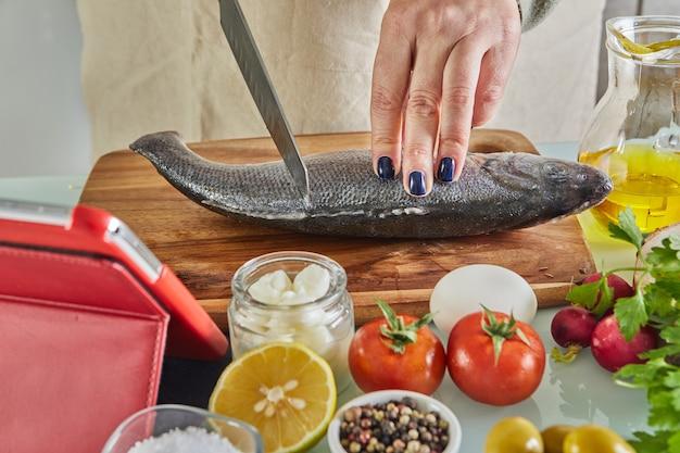Frau kocht nach dem tutorial der virtuellen online-meisterklasse, und schaut auf das digitale rezept, unter verwendung des touchscreen-tablets, während gesundes essen auf der küche zu hause kocht.