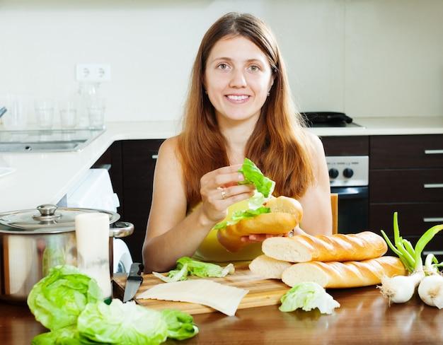 Frau kocht sandwiches mit käse und gemüse