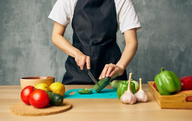 Frau kocht schwarze schürze, die gemüse schneidet, schneidet brettküche kochendes essen