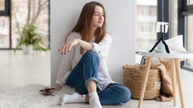 Frau kommt mit neuen ideen für einen blog auf dem boden