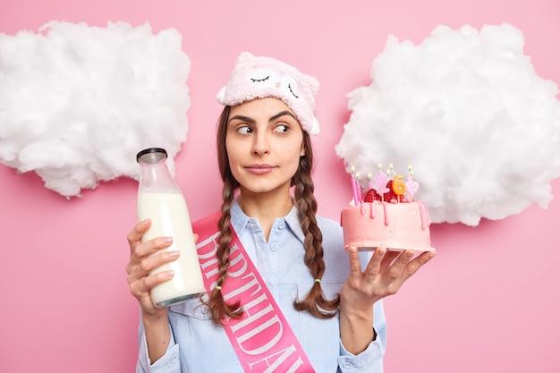 Frau konzentriert beiseite hält köstlichen kuchen und eine flasche milch, die an ihrem geburtstag ein festliches abendessen haben wird, trägt ein schlafmaskenhemd isoliert auf rosa