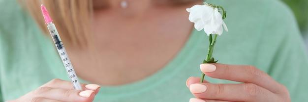 Frau kosmetikerin hält spritze mit medizin und verwelkte blume in ihren händen nahaufnahme