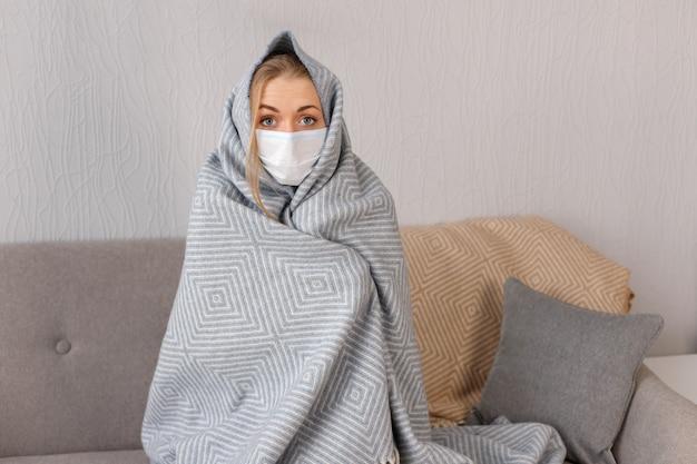 Frau krank zu hause in medizinischer maske und decke