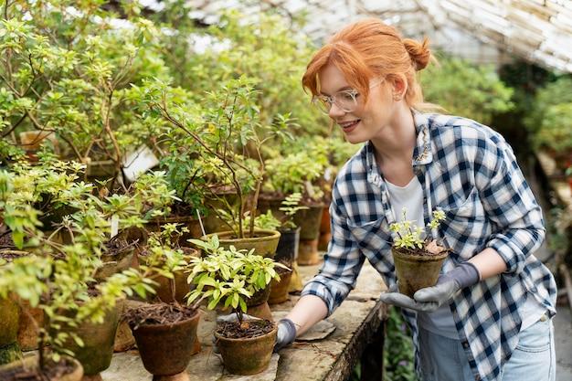 Frau kümmert sich um ihre pflanzen in einem gewächshaus