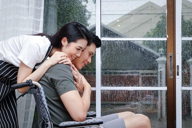 Frau kümmert sich um ihren behinderten ehemann sitzen auf einem rollstuhl in ihrem haus