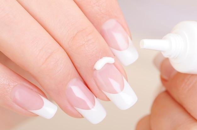 Frau kümmert sich um ihren finger, der die feuchtigkeitsspendende kosmetische creme auf fingernagel anwendet