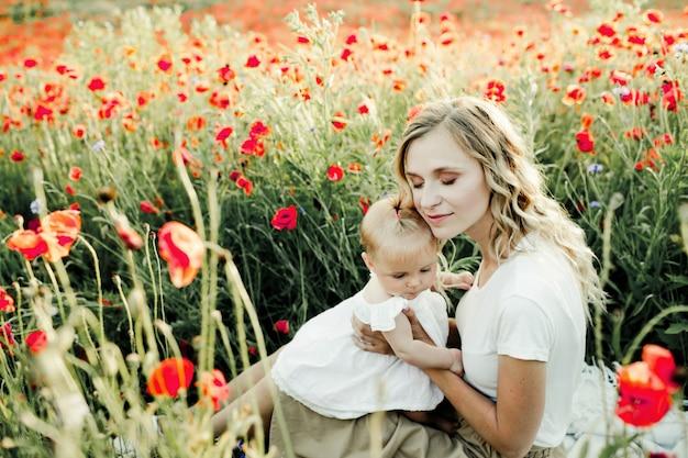 Frau kuschelt sich an ihr baby auf dem mohnblumenfeld