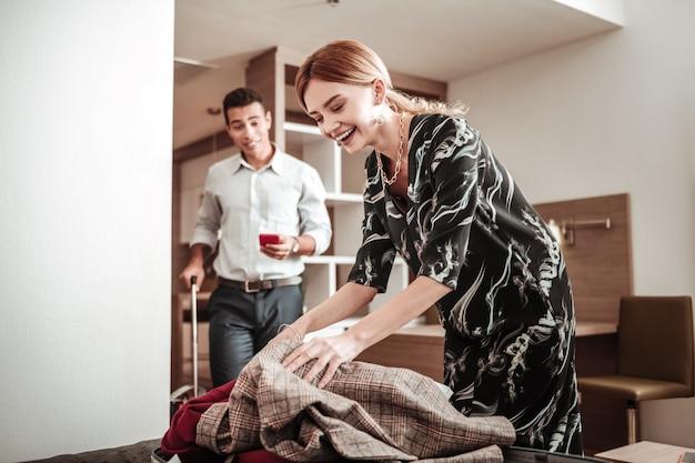 Frau lacht. ansprechende strahlende frau, die lacht, während sie ihr gepäck packt, das geschäftsreise mit ihrem mann hat