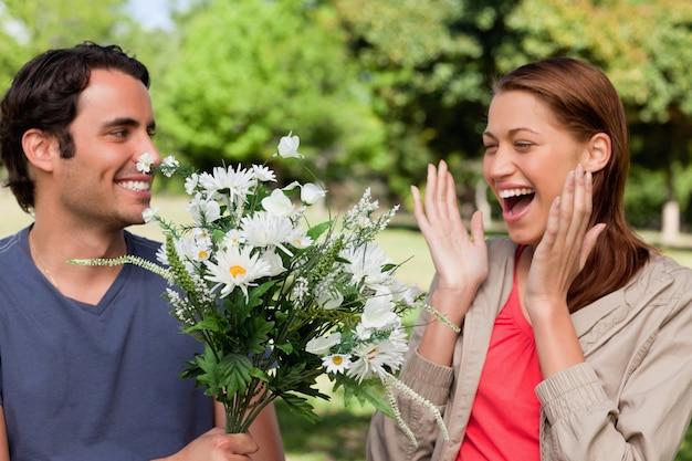 Frau lacht aufgeregt, als sie von ihrem freund mit blumen präsentiert wird